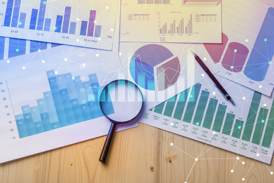 Magnifying glass and documents with analytics data lying on table,selective focus