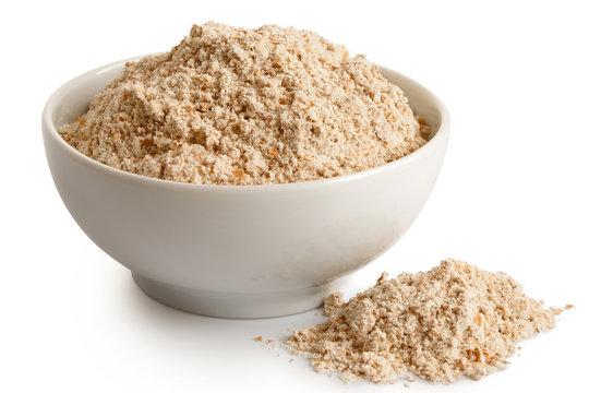 Spelt whole grain flour in white ceramic dish isolated on white. Spilled flour.