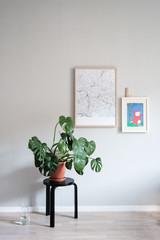 Zimmer mit Alvar Aalto Hocker, Monstera und Bildern