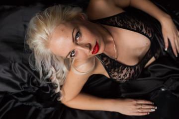 sexy blonde in black Silk Underwear lies on bed
