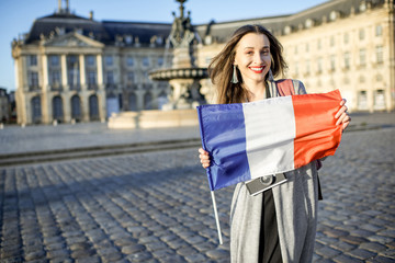 Young and happy woman tourist holding french flag in Bordeaux city in France