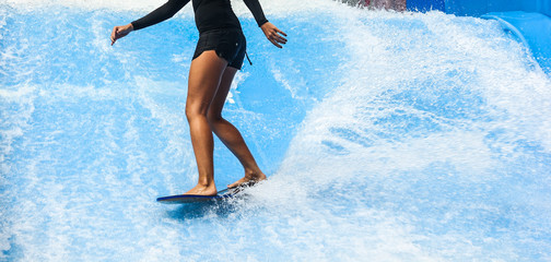 Girl on black swimsuit surfing on wave pool with small board in the island of Phuket, Thailand
