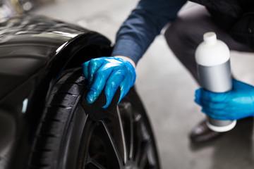 Man washing car tyres