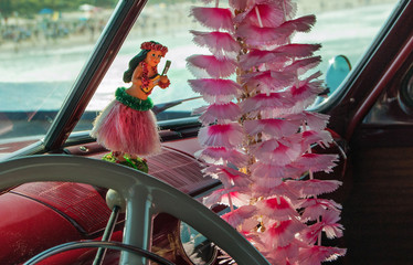 Hula girl toy on dashboard of classic car in Hawaii