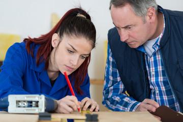 Teacher watching apprentice mark position on wood