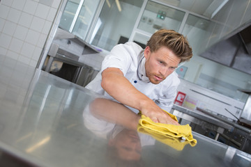 Chef polishing stainless steel work surface