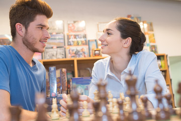 Young couple behind chess pieces