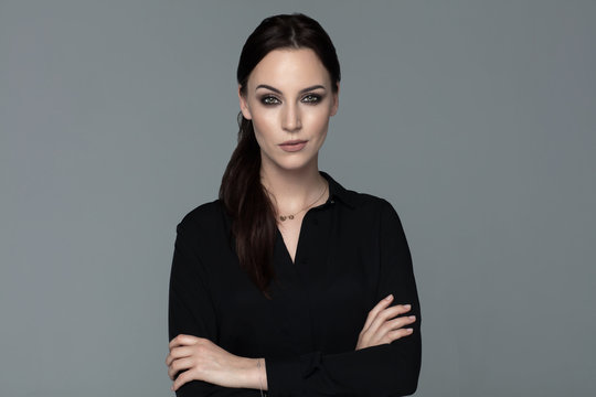 Brunette woman with arms crossed wear black shirt isolated on grey