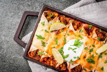Mexican food. Cuisine of South America. Traditional dish of spicy beef enchiladas with corn, beans, tomato. On a baking tray, on a black stone background. Top view copy space