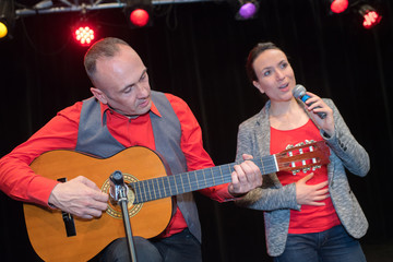 Man playing guitar and woman singing on stage