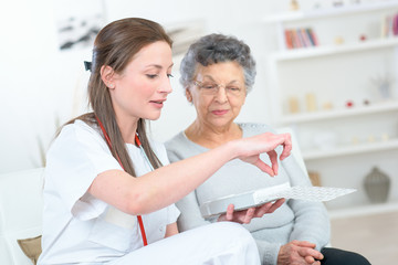 Nurse discussing medication with elderly woman
