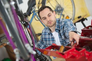 Mechanic reaching for tool to repair bicycle