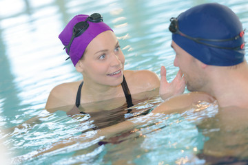 Two swimmers talking in pool