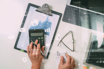 top view of businessman hand working with finances about cost and calculator and latop with mobile phone on withe desk in modern office with VR icon diagram