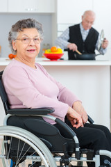 Portrait of elderly lady in wheelchair, husband cooking