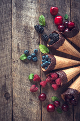 Fresh fruits in the ice cream cones on wooden background with blank space