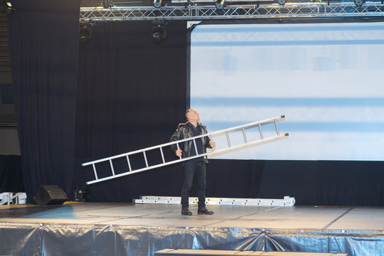 Man carrying ladder onto theatre stage