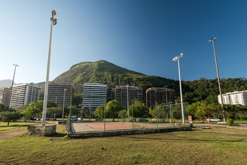 Small Football Field With Apartment Buildings and a Mountain in Background