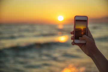 woman's hand holding smartphone to taking sunset photo on the beach. mobile phone with view on screen at sunset