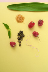Ripe raspberries, sugar, mint leaves and a scattering of green tea on a pastel yellow-green background.