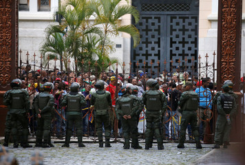 Government supporters stand outside the gates of the National Assembly as they besiege the building in Caracas