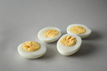 Sliced hard boiled eggs on grey background. Nutrition concept