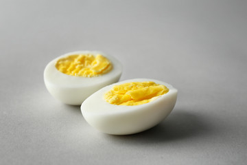 Sliced hard boiled egg on grey background. Nutrition concept