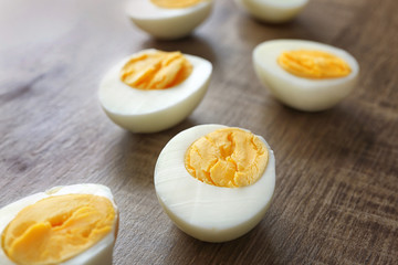 Sliced hard boiled eggs on wooden surface. Nutrition concept