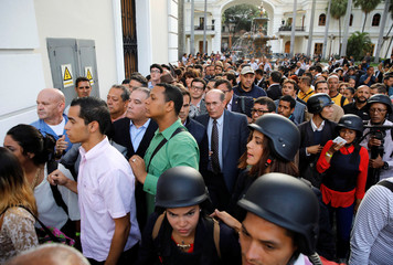 People stand in line to leave the National Assembly after government supporters were moved back by security forces in Caracas