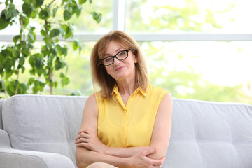 Attractive mature woman resting on sofa at home