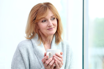 Attractive mature woman with cup of coffee standing near window at home