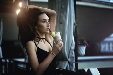 Woman drinking chocolate milkshake with fruit in a cafe outdoors