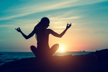 Yoga silhouette during amazing sunset. Meditation woman on the ocean. Fitness and healthy.