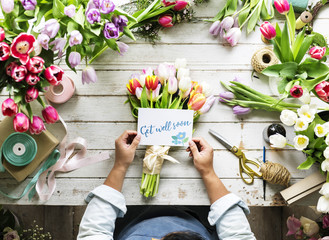 Florist Making Fresh Flowers Bouquet Arrangement with Get Well Soon Wishing Card