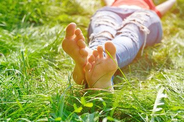 feet of the woman resting in green grass