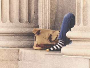 Homeless Man On Street Next To Building With Striped Socks And A Bag