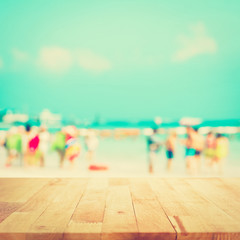 Wood table top with blurred people at the beach as background, vintage tone