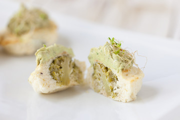Mini cauliflower casseroles with avocado cream on a white plate