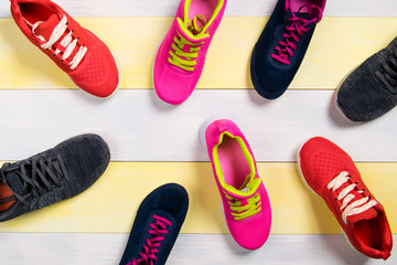 Scattered sports shoes on a multi-colored floor, background
