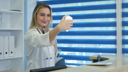Smiling nurse taking selfies with her phone behind reception desk
