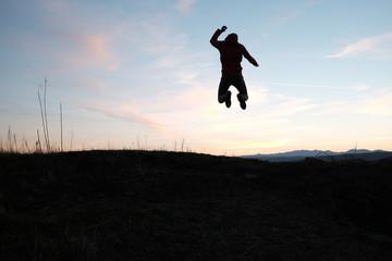 Homme sautant face au coucher de soleil