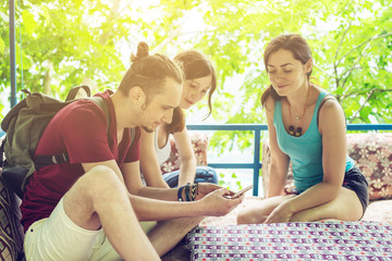 A group of young people relax outdoors and watch videos from your phone. Friends smile and laugh together