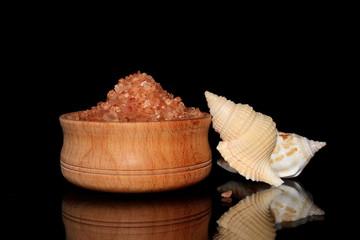 морская розовая соль в миски на черном фоне с ракушкой