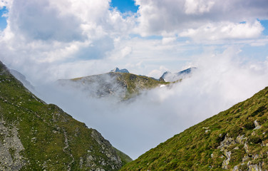 high mountain peak in clouds among the hills