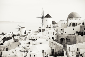 Traditional Oia windmills in Santorini, sepia toned black and white photo