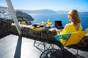 Woman working with laptop while on vacation in Mediterranean