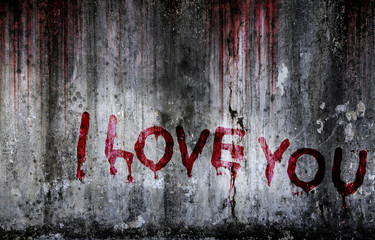 Write a message I love you on bloody background scary old wall, concept of disappointed in love and horror