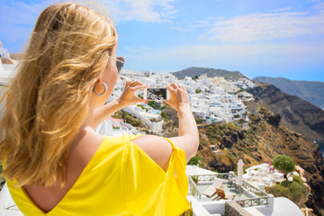 Woman taking picture of Santorini.