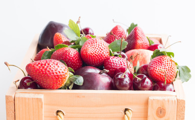 Mixed fresh fruits in box on white background