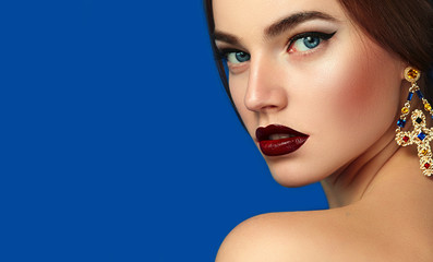 Portrait of a beautiful young girl on a blue background. Ornaments, bijouterie - large earrings-crosses in Byzantine style. Makeup - dark burgundy lipstick, arrows on the eyes.